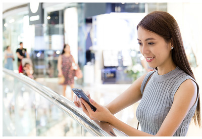 Chinese young woman using smartphone at mall